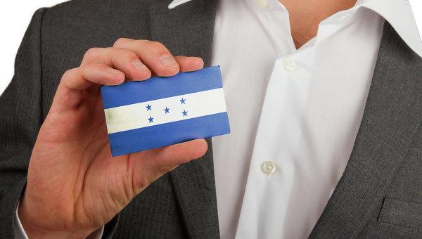 Мужчина держит карточку с флагом Гондураса