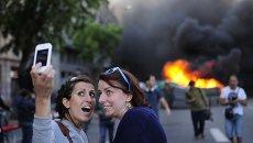 Туристы фотографируются на фоне горящего контейнера во время майской демонстрации в Барселоне, Испания