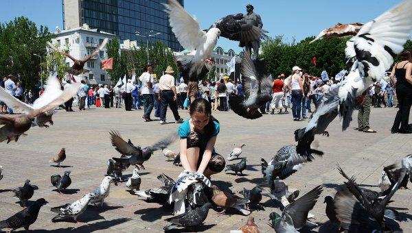 Девочка кормит голубей во время митинга в Донецке. Архивное фото