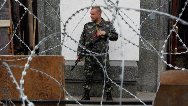 Ополченец Луганской Народной Республики возле здания городской администрации в Луганске