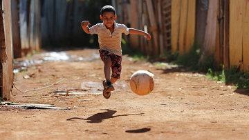 Мальчик играет в футбол в трущобах города Бразилиа. Архивное фото