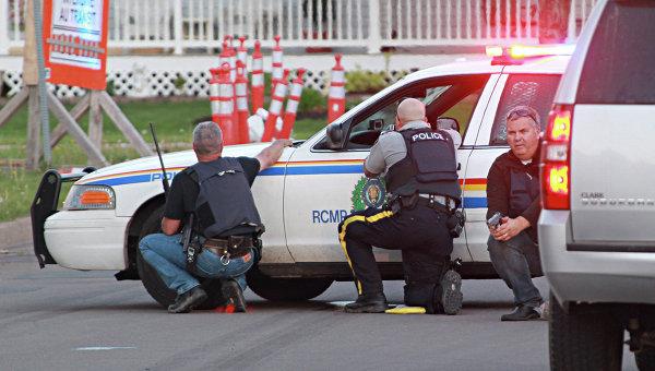 Полицейские на позициях за служебными машинами в городе Монктон, провинция Нью-Брансуик, Канада. Архивное фото