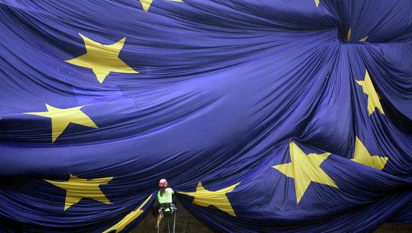 Рабочий закрепляет на фасаде здания флаг Евросоюза