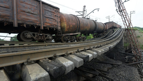 Провисший над взорванным железнодорожным мостом в Донецкой области грузовой состав. Архивное фото