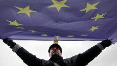 Мужчина держит флаг Евросоюза, архивное фото