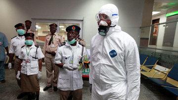 Медицинские работники и сотрудники аэропорта ожидают пассажиров в международном аэропорту в Лагосе, Нигерия