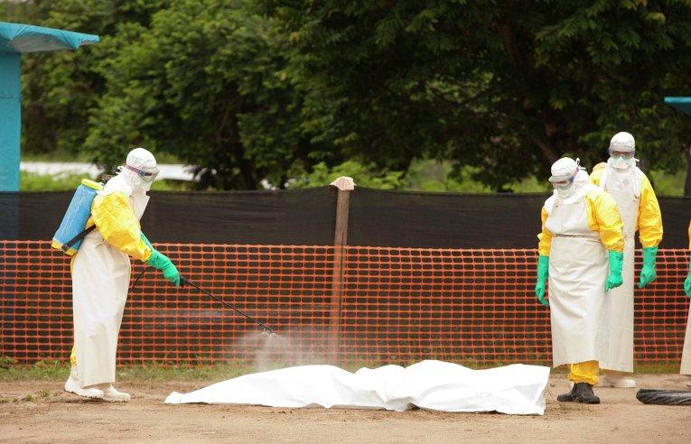 Медики дезинфицируют тело умершего от вируса эбола в Либерии