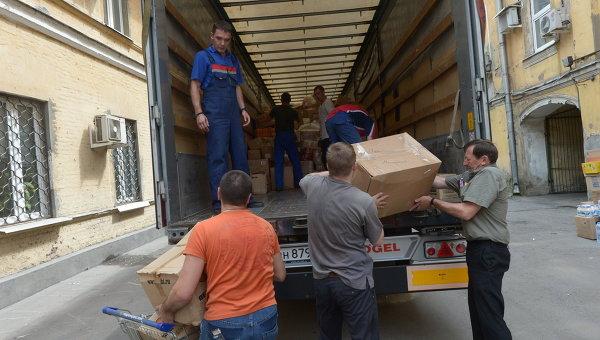 Рабочие загружают в грузовой автомобиль гуманитарную помощь для граждан Украины