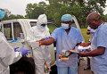 Медицинские работники передают средства индивидуальной защиты от лихорадки Эбола в Либерии