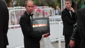 Служитель на дорожке держит работающий телевизор