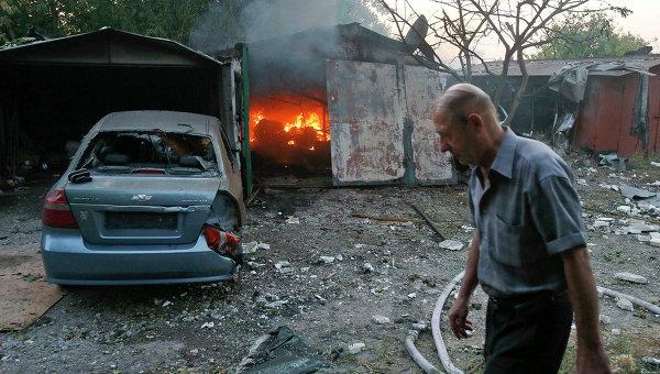 Житель у горящего в результате обстрела Украинскими военными строения в Донецке
