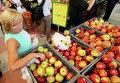 Женщина покупает яблоки в магазине в Варшаве. 6 августа 2014