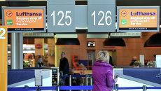 Пассажирка стоит у стойки регистрации авиакомпании Lufthansa