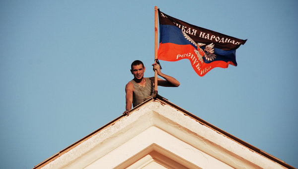 Ополченец ДНР устанавливает флаг ДНР на здании мэрии города Комсомольское Донецкой области. Архивное фото