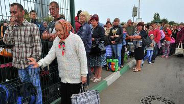Украинские беженцы стоят в очереди на границе для возвращения в свои дома. Архивное фото