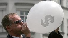 Человек в костюме надувает воздушный шар со значком американского доллара во время уличного шоу в центре Берлина. Архивное фото