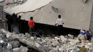 Сирийские жители осматривают разрушенные авиаударами США здания