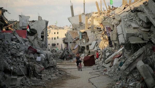 Мальчик на фоне разрушенных домов в Секторе Газа