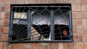Женщина смотрит из окна своего дома, разрушенного после обстрела украинскими силовиками в Донецке, Архивное фото