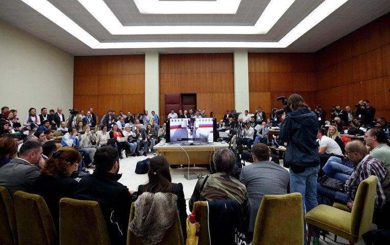 Журналисты наблюдают на экране телевизора церемонию встречи Владимира Путина в Белграде