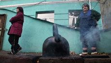 Люди кипятят воду возле входа в бомбоубежище в Донецке