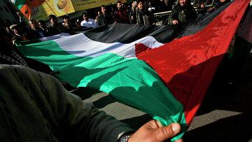 Палестинцы с национальным флагом на улице Газы. Архивное фото.