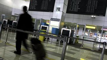 Турист с чемоданом в аэропорту. Архивное фото
