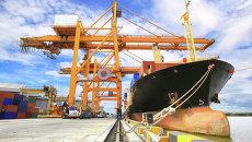 Погрузка контейнера на торговое судно. Архивное Фото.