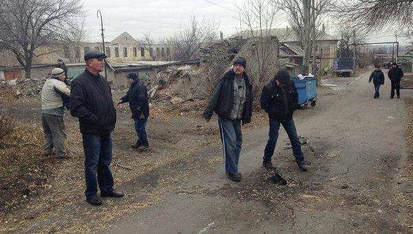 Жители микрорайона Азотный рассматривают осколок града после обстрела, в котором погибли 12-летний мальчик и 55-летняя женщина
