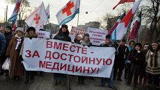 Митингующие несут плакат с надписью Вместе за достойную медицину!. Архивное фото