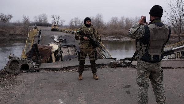 Украинские военные фотографируются на фоне разрушенного моста через реку Северский Донец. Архивное фото