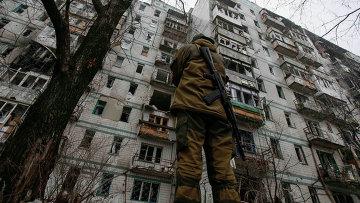 Боец ополчения возле поврежденного обстрелами дома в районе Донецкого аэропорта