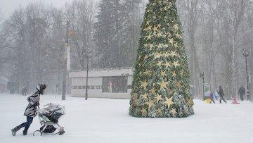Женщина с коляской во время снегопада в Москве