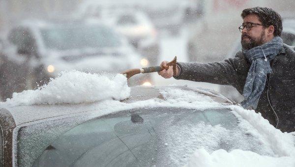 Автовладелец счищает снег с автомобиля. Архивное фото