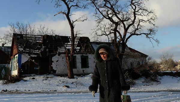 Женщина проходит мимо здания, разрушенного в результате боевых действий в деревне Степановка, Украина. Архивное фото