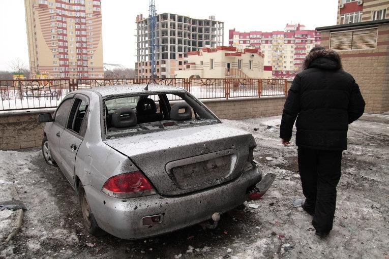 Мужчина рядом с поврежденным автомобилем после артобстрела Донецка