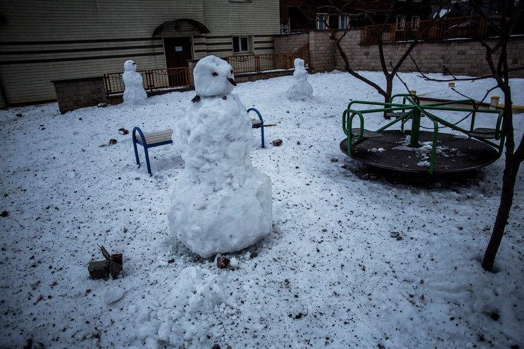 Снеговик на детской площадке, усыпанной осколками артиллерийских снарядов, после обстрела Донецка