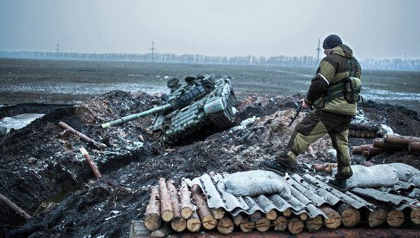 Ополченец стоит у танка украинской армии в Донецкой области. 5 февраля 2015