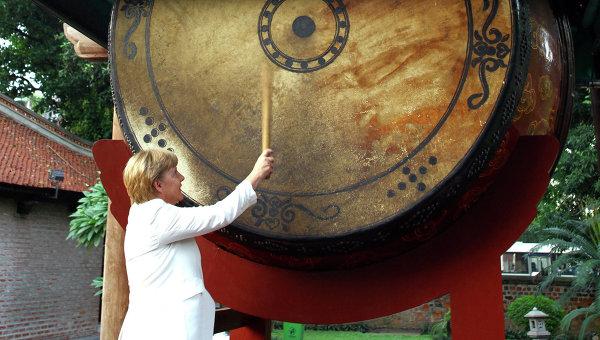 Канцлер Германии Ангела Меркель бьет в гигантский барабан во время визита во Вьетнам. Архивное фото