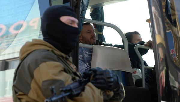 Ополченец охраняет автобус с украинскими силовиками во время обмена пленными. Архивное фото