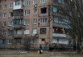 Женщина проходит мимо разрушенного жилого дома в Авдеевке, Украина