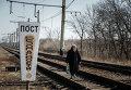 Женщина идет по железнодорожным путям недалеко от Дебальцево
