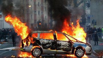 Горящая полицейская машина во время беспорядков во Франкфурте. Архивное фото