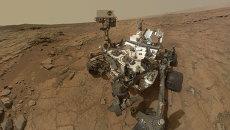 Марсоход Curiosity во время изучения камня Джон Кляйн на поверхности красной планеты