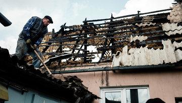 Мужчина убирает мусор с крыши дома, который подвергся обстрелу. Донецк, Украина. Архивное фото