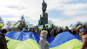 Участники демонстрации держат флаг Украины у памятника Тарасу Шевченко в Харькове. Архивное фото