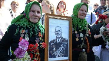 Ветераны Великой Отечественной войны с портретом маршала Георгия Жукова в парке Вечной Славы в Киеве . Архивное фото