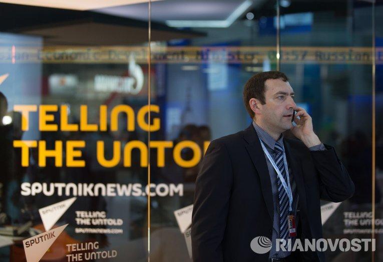 Участник форума разговаривает по телефону у павильона новостного агентства Sputnik на XIX Петербургском международном экономическом форуме