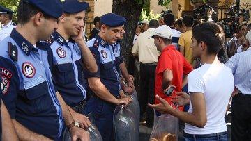 Горожанин предлагает выпечку сотрудникам правоохранительных органов во время масштабной акции протеста против повышения тарифов на электроэнергию