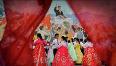 Студенты танцуют на фоне изображения Ким Ир Сена в Пхеньяне, КНДР